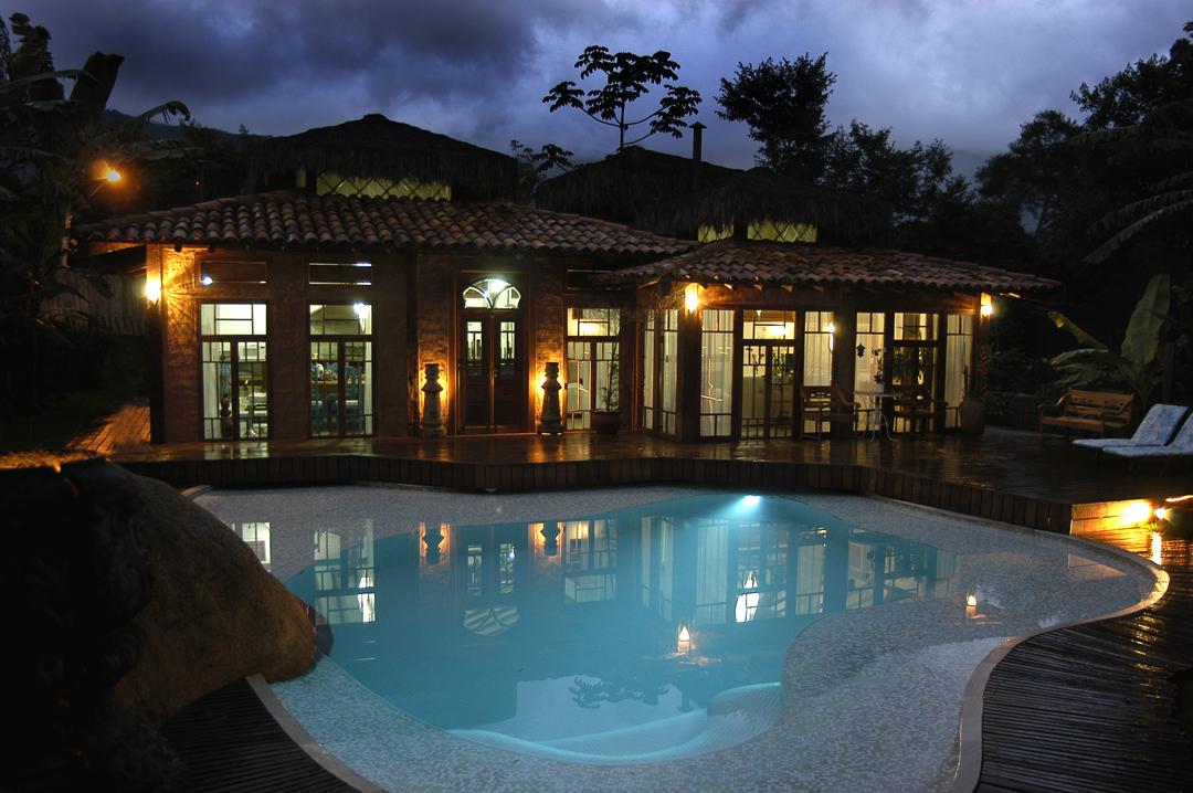 Vista noturna de piscina e fachada